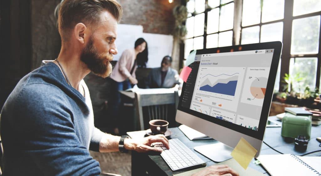 Homme barbu derrière un ordinateur