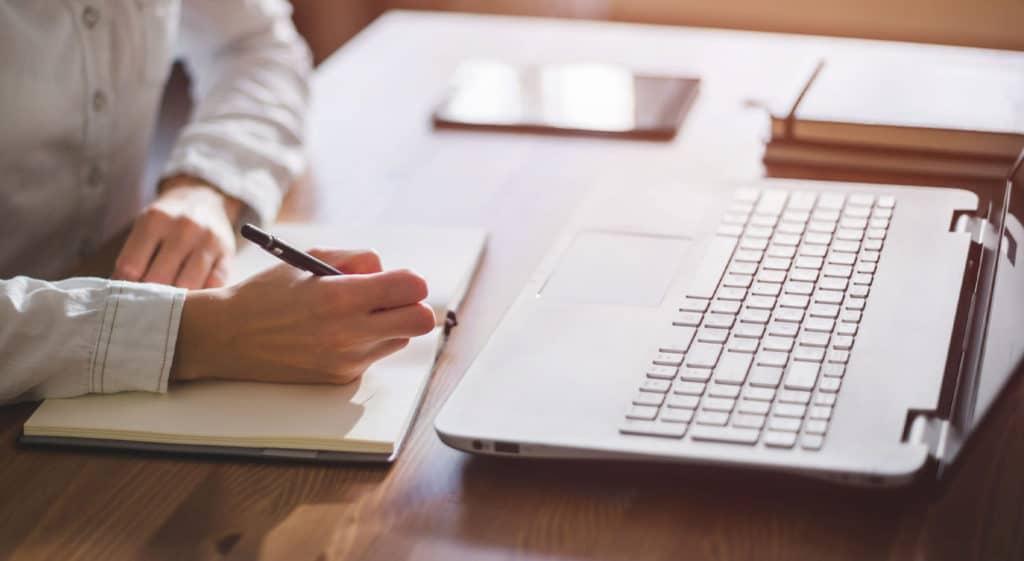 Mains de femmes qui écrit sur un carnet devant un ordinateur