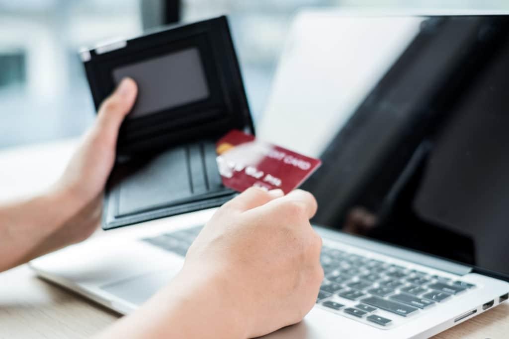 Femme d'affaires tenant une carte bancaire dans sa main pour payer le concepteur de son site vitrine