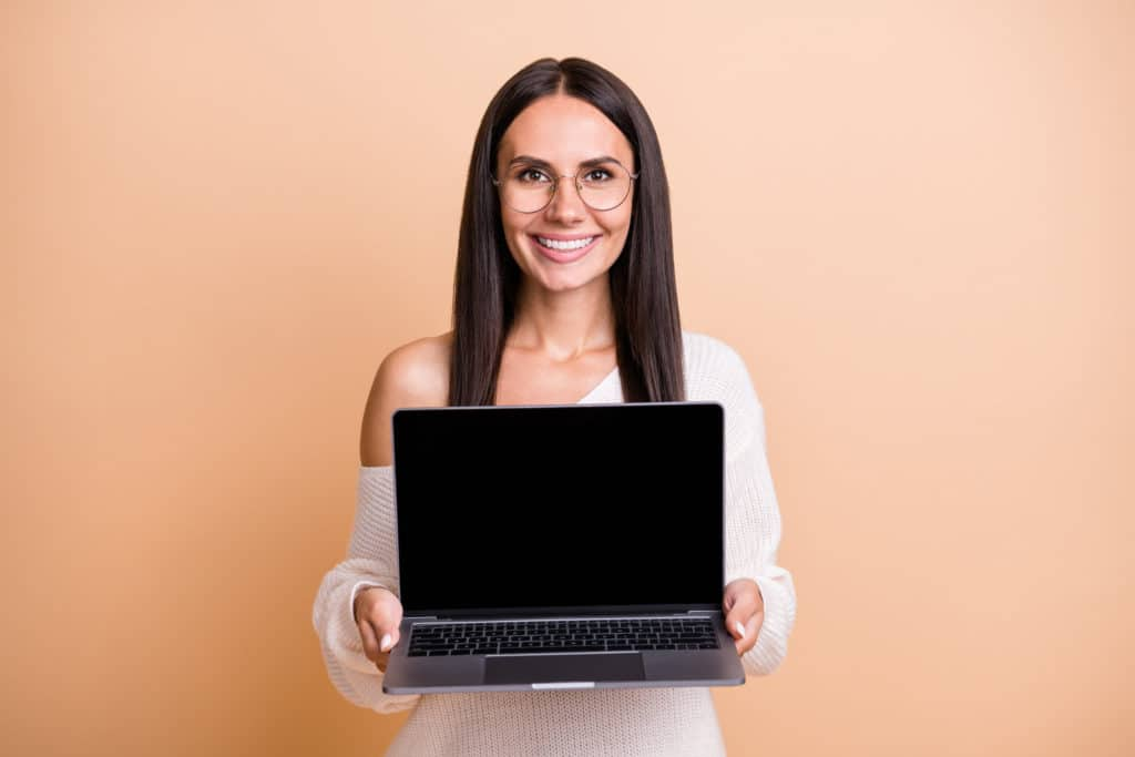Femme d'affaires souriante tenant son laptop sur un fond beige